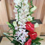 Notre fleuriste a réalisé cette composition en hauteur avec des fleurs exotiques dans les tons rouge et blanc