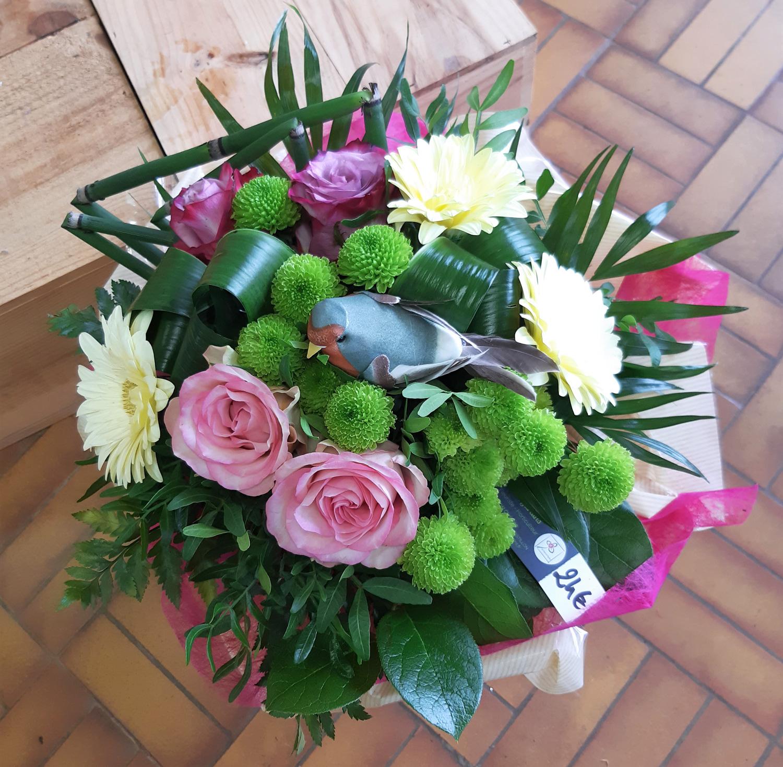 Bouquet dans les tons rose et vert avec un oiseau